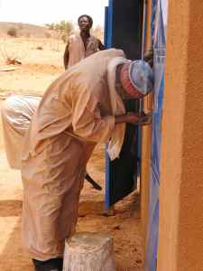 Locking up his first house, a leprosy affected man in Niger