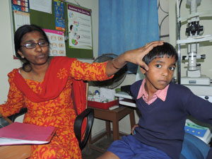 Dr Helen Roberts diagnosing Akash Singh (eight) with leprosy