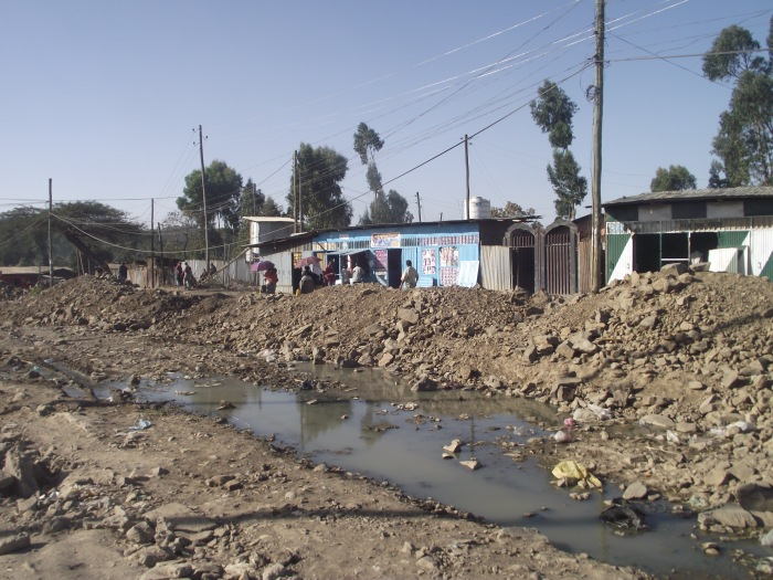 Another view of the slum showing stagnant water - a breeding ground for disease.