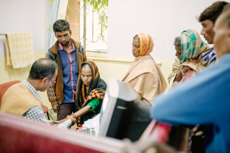 A woman undergoes a consultation while other patients queue around her.