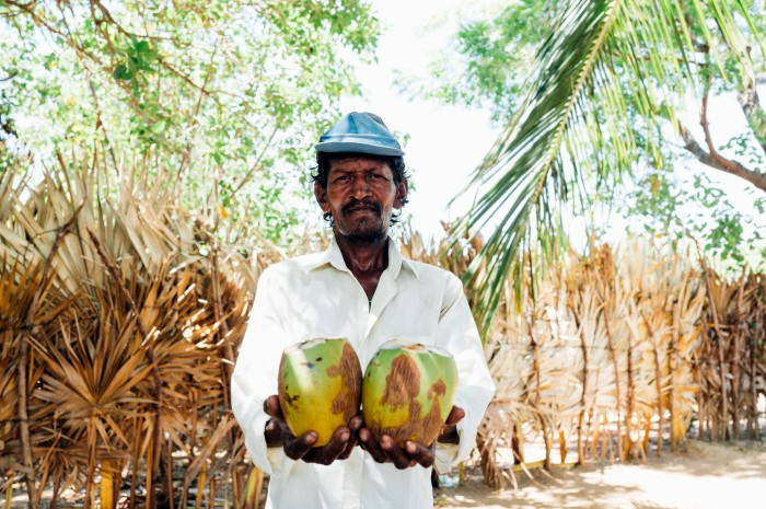 Kunam with some of the coconuts he is now growing thanks to your support.